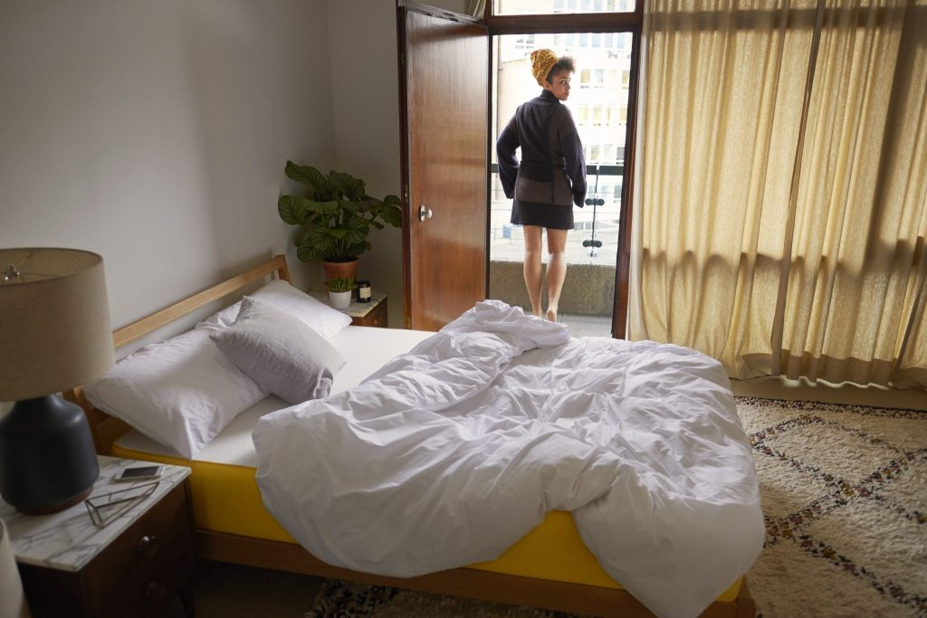 Woman in hotel room balcony on holiday with eve mattress in room