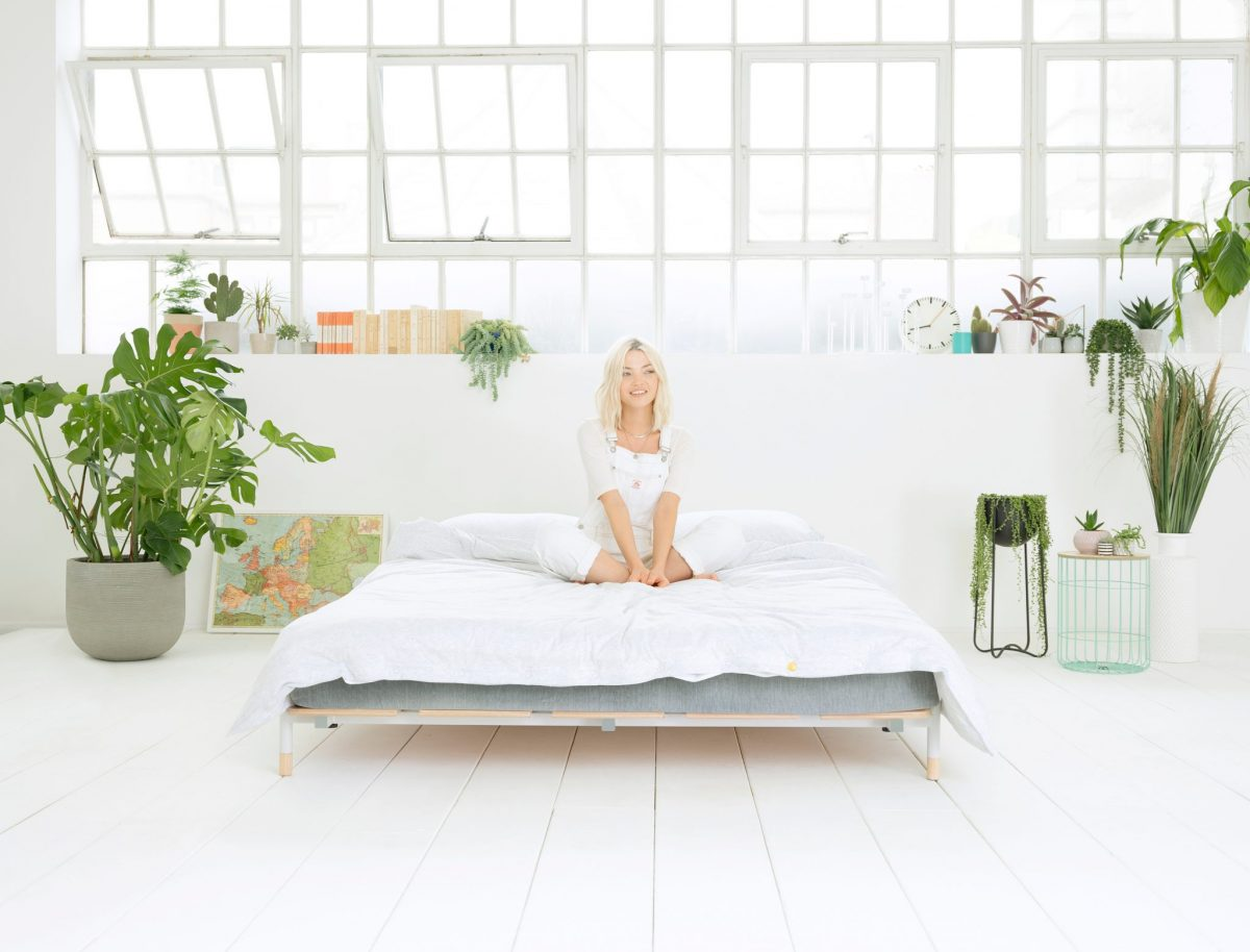 girl sat on eve hybrid mattress and modular bed frame