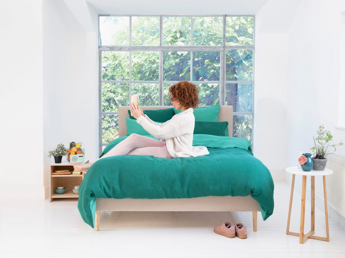 woman reading book on eve mattress and eve bed frame
